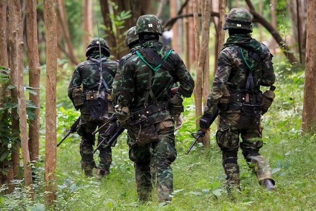 숲에서 반올림 총을 가진 제복을 입은 군인 프리미엄 사진