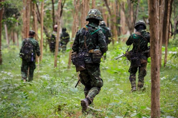 숲에서 반올림 총을 가진 제복을 입은 군인