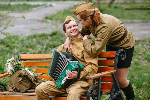 Soldier is sitting on a bench, playing an accordion and female solider behind
