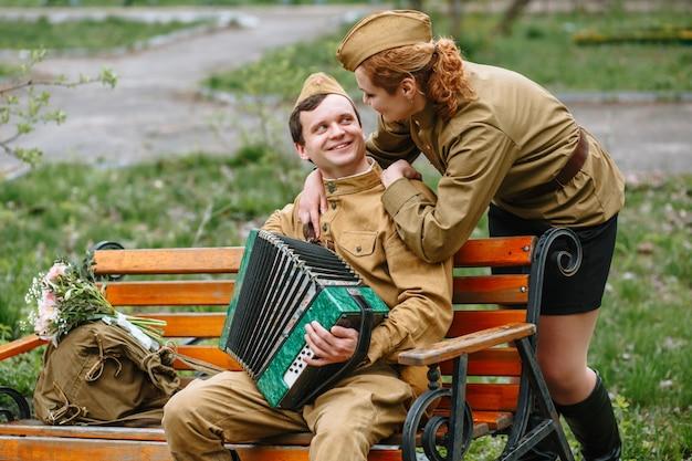 兵士はベンチに座って、アコーディオンと背後に女性兵士を演じています