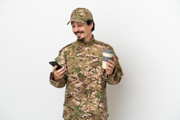 持ち帰り用のコーヒーと携帯電話を保持している白い背景で隔離の兵士の男