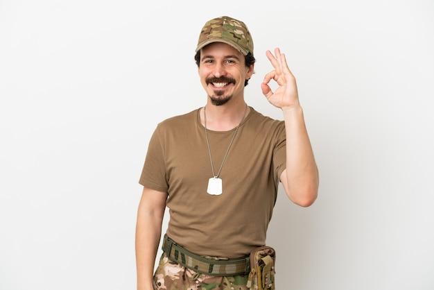 Человек-солдат, изолированные на белом фоне, показывает знак ок пальцами
