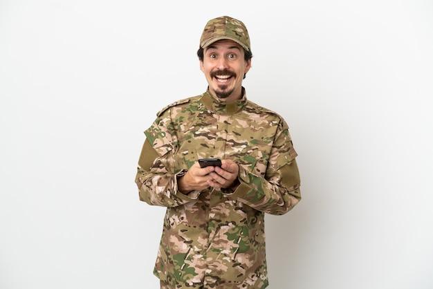 흰색 배경에 고립 된 군인 남자 놀라고 메시지를 보내는