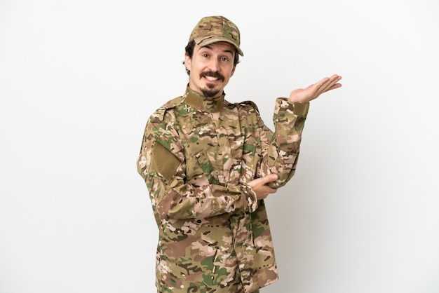 Soldier man isolated on white background extending hands to the side for inviting to come