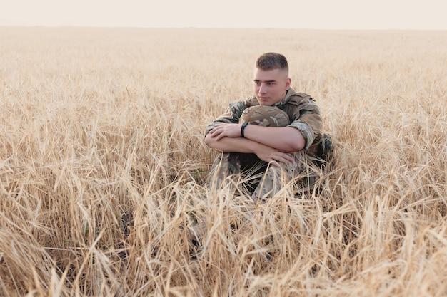 필드에 서있는 군인 남자. 부트 캠프에서 행복 군사 군인의 초상화입니다. 임무에서 미 육군 병사. 전쟁과 감정적 개념.