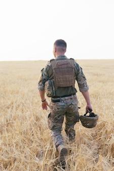 필드에 서 있는 군인 남자. 신병 훈련소에서 행복 한 군인의 초상화입니다. 미션에서 미군 병사. 전쟁과 감정적 개념.
