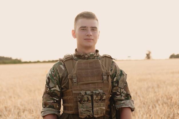필드에 서 있는 군인 남자. 신병 훈련소에서 행복 한 군인의 초상화입니다. 미션에서 미군 병사