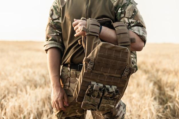 필드에 서 있는 군인 남자. 방탄 조끼와 군사 복장에 군인입니다. 오렌지 사막 배경에 총과 방탄 조끼를 들고 군사 복장에 군인의 사진.