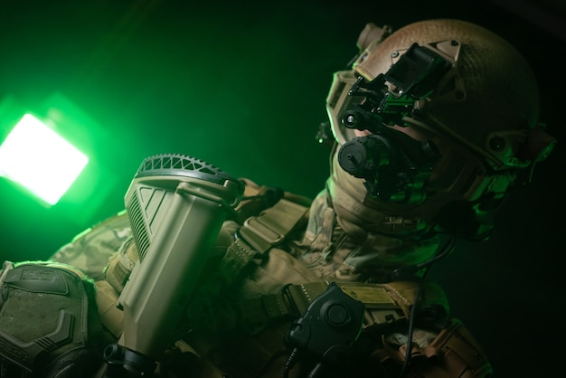 The soldier in military clothing with a night vision device and on a dark background