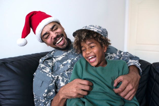 Soldier in military uniform enjoying christmas holiday with his daughter