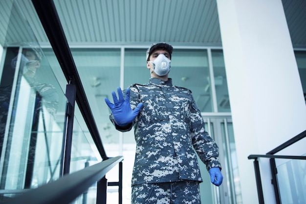 Soldier in military uniform with rubber gloves and face protection mask guarding hospital doors and gesturing stop sign