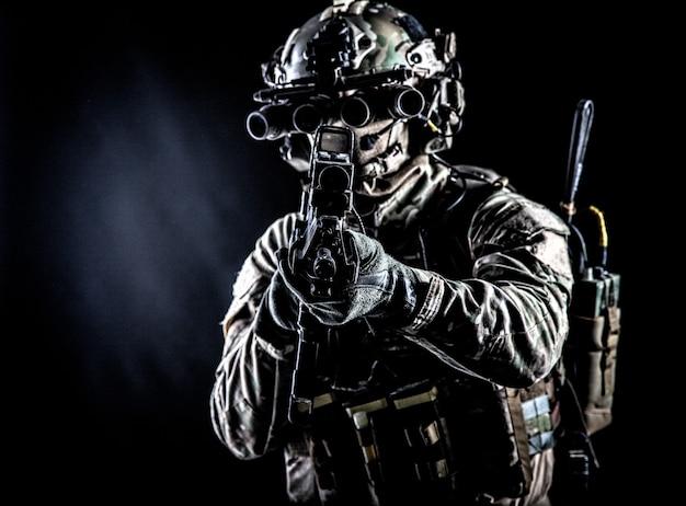 Солдат спецназа в камуфляжной боевой форме, багажник, каска, экипированные очки ночного прицела, тактическая радиогарнитура, прицельная винтовка с коллиматорным прицелом в камеру, сдержанная студийная съемка