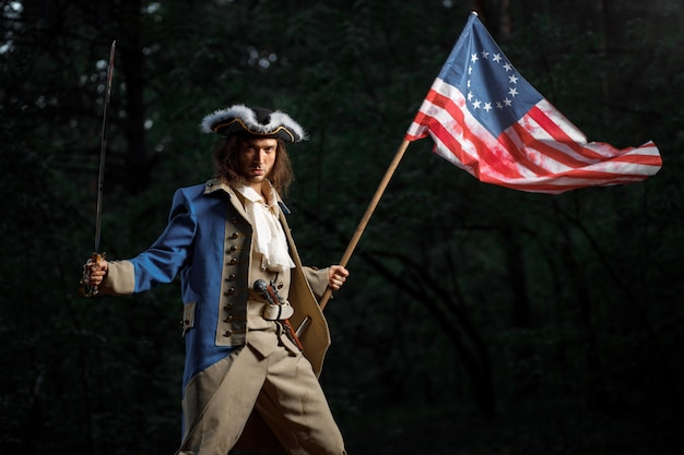 Soldier patriot rebel during war of independence of united states with flag preparing to attack with saber