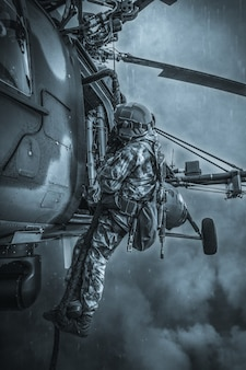 Soldier prepares to jump from a helicopter. the concept of computer games. mixed media