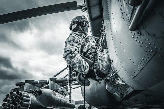 兵士はヘリコプターから飛び降りる準備をしています。コンピュータゲームの概念。ミクストメディア