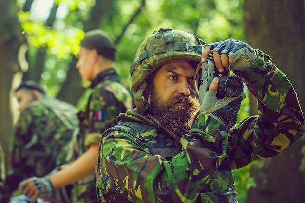 カメラを手に真面目な顔をした兵士記者。