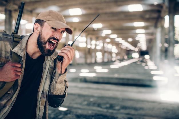 ポータブルラジオで叫んでいる兵士。大きなライフルが肩にかかっています。