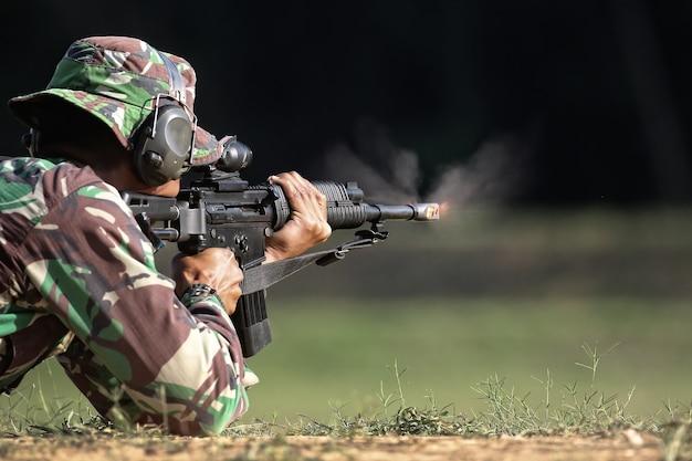 Солдат стреляет из пистолета с огнем и дымом в дуло