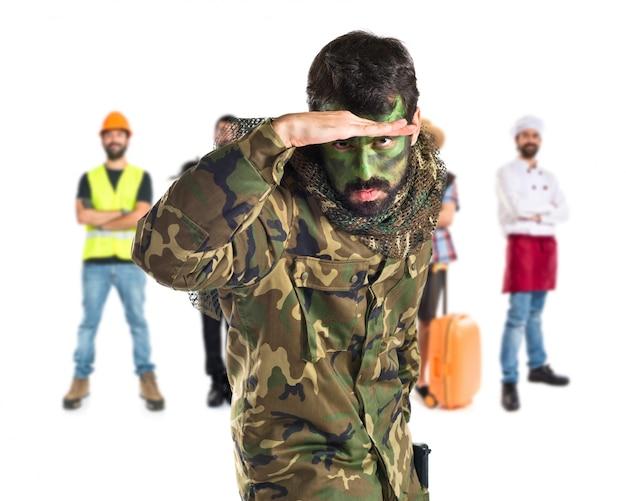 Soldato mostrando qualcosa su sfondo bianco