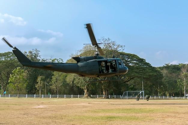 군인은 헬리콥터 기동에 앉아 있습니다.