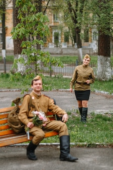 A soldier in a soviet military uniform sits on a bench
