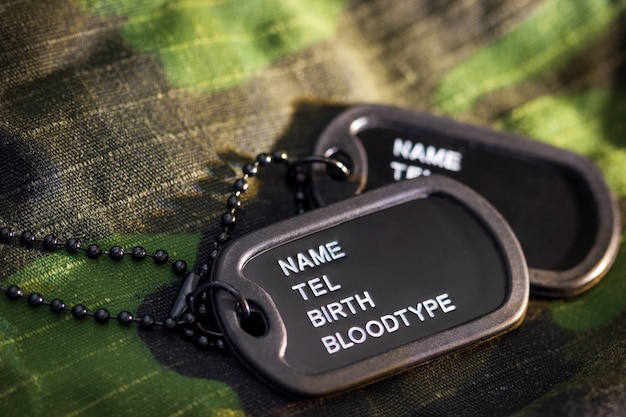Soldier tag or dog tag laid on military jacket and morning sunlight.