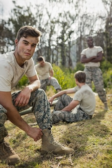 Soldier tying his shoe laces in boot camp
