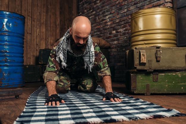 Soldier in uniform praying before terrorist attack