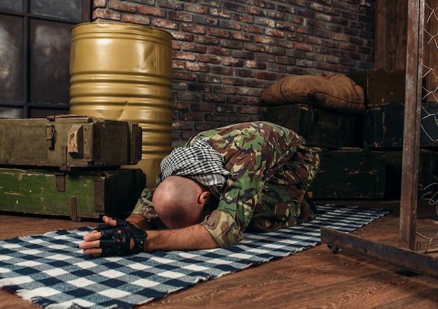 Soldier in uniform praying before a terrorist attack
