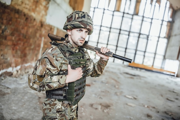 A soldier in uniform wears a big rifle in his hands.