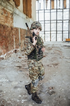 A soldier in uniform wears a big rifle in his hands