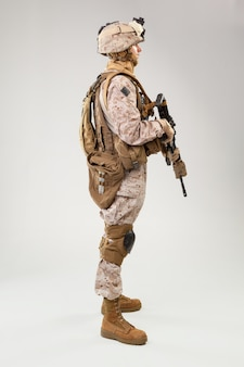 Soldier in us marines uniform with rifle on light grey , studio shot