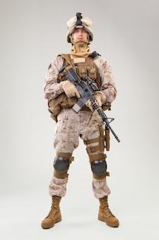 Soldier in us marines uniform with rifle on light grey wall,