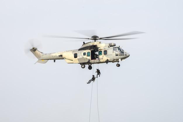 軍用ヘリコプターから攻撃するために下がるロープを使用している兵士