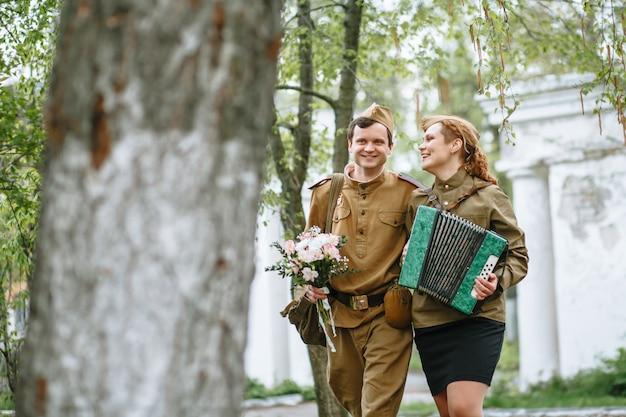 兵士が路地を歩き、アコーディオンを弾く軍人女性を抱き締める