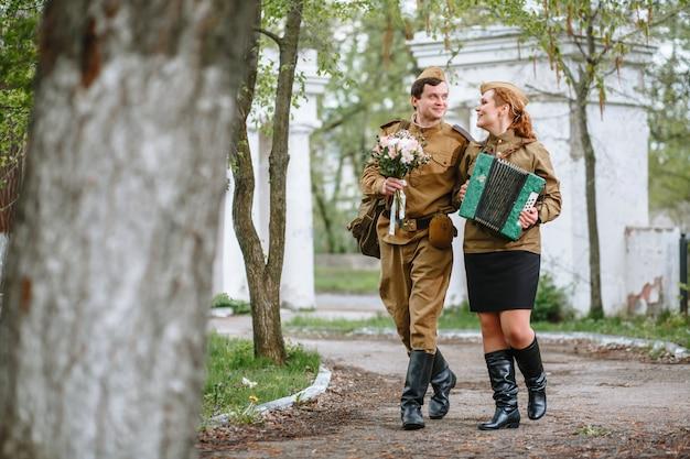 Солдат идет по аллее, обнимая военную женщину, играющую на аккордеоне