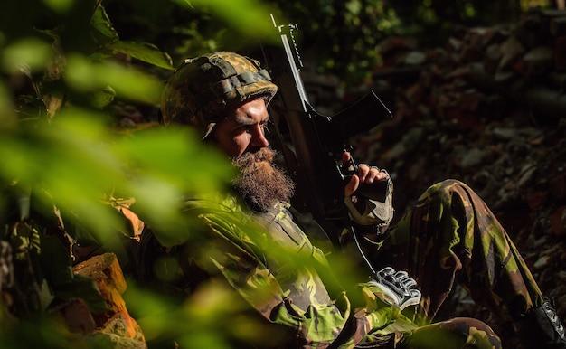 軍用ヘルメットと銃でカモフラージュの悲しい顔を持つ兵士