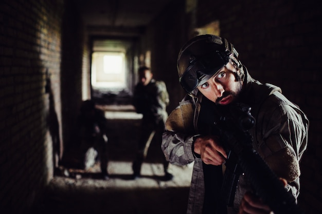Soldiers are standing in dark corridor and waiting.