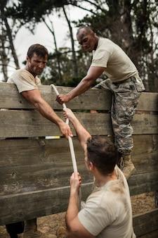 Солдаты взбираются на деревянную стену с веревкой