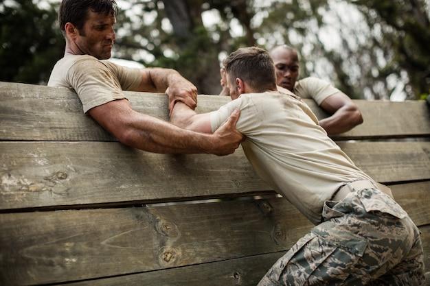 Солдаты помогают человеку подняться на деревянную стену