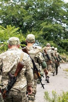 完全な弾薬のシェブロンとカラシニコフのアサルトライフルを備えた制服を着たウクライナ軍の兵士が配備場所に行きます。