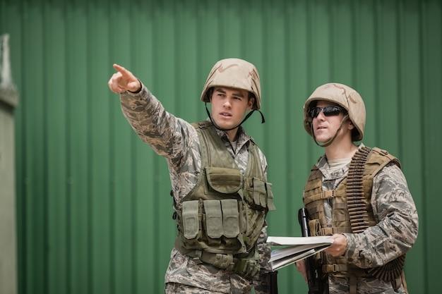 Солдаты показывают направление своему коллеге в учебном лагере