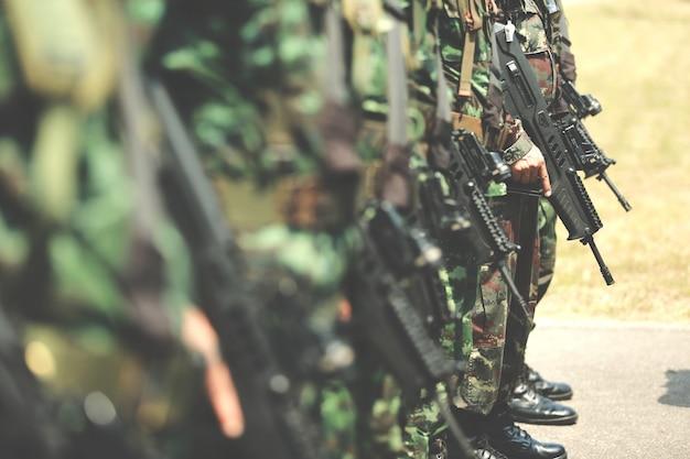 군인들이 줄을 서 있습니다. 손에 총. 육군, 군사 부츠 라인 코만도 군인. 프리미엄 사진