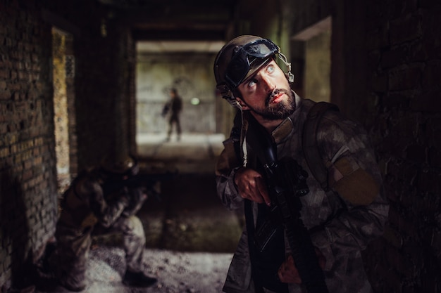 Soldiers standing in dark corridor of empty building. bearded guy is looking up and holding rifle.