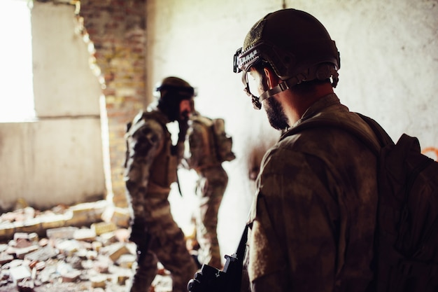 Soldiers standing in a rooom near ruined wall.