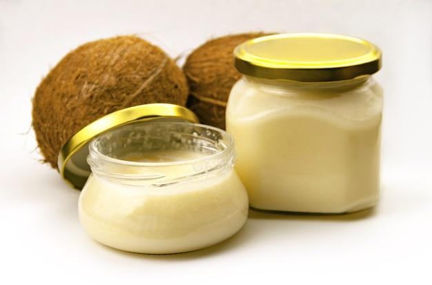 금속 금 뚜껑이 달린 유리 항아리에 단단한 수제 코코넛 오일과 흰색에 신선한 코코넛이 가까이 있습니다. 선택적 소프트 포커스. . 텍스트 복사 공간. 코코넛 버터 개념