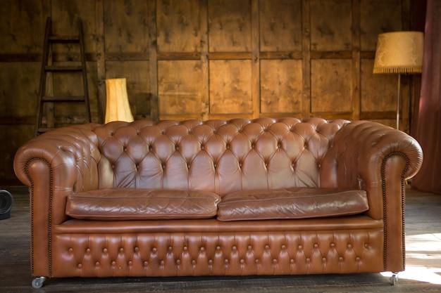 木製のインテリアで無垢の革のソファ。家やオフィスのロフトスタイルのインテリアで茶色のソファ