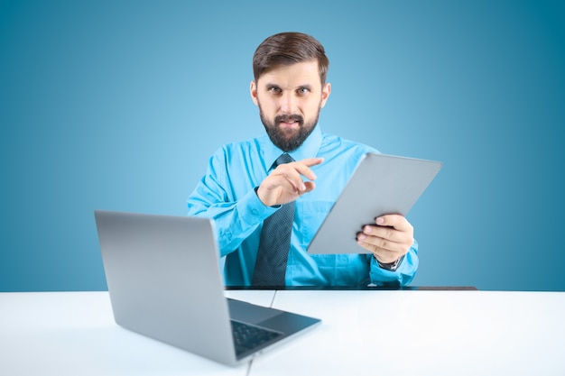 A solid man in an office at a computer holds a tablet in one hand and clicks on it when performing financial reports