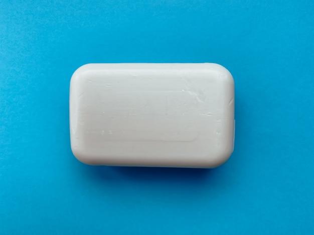 青い背景の手のための固体石鹸。衛生とケア。