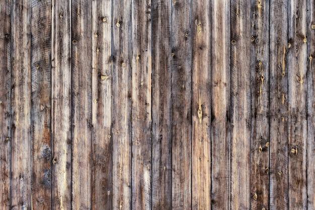 울타리를 형성하는 비트 자국이있는 진한 갈색의 단단한 나무 널빤지
